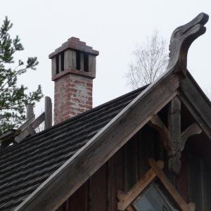 skorsten och taknock. Ett utsnidat fantasidjur (huvud) pryder gaveln på taket.