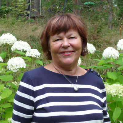 Ann-Christine Westerlund i sin trädgård i Karis. Hennes andra hem finns i New York