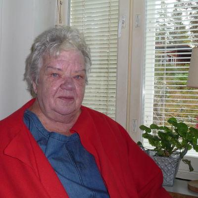 Rosie Westerlund vid sitt köksfönster, pelargoner och bordslampa  på fönsterbrädet