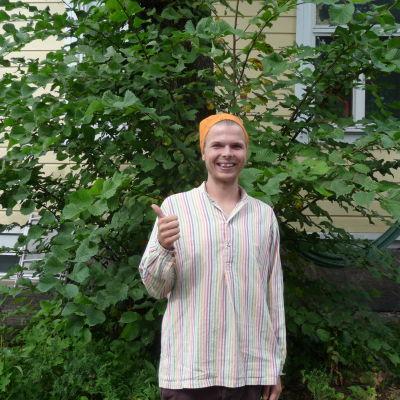 Andreas Wiberg i sin trägård i Åbo. Visar tummen upp och ler.