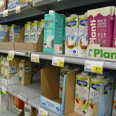 en butikshylla med några olika sorter och kartonger av växtmjölk.