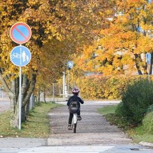 Ett barn kör med cykel längs med en trottoar i Närpes.