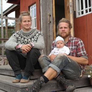 Julia Ajanko och Lennart Söderlund sitter med sin baby på trappan till caféet på Brännskär