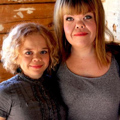 Linda ja Katriina hymyilevät kameralle. Taustalla kartanorakennuksen hirsiseinä.
