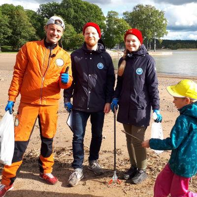 Programledaren Jontti Granbacka står på Runsala strand tillsammans med representanter för Håll Skärgården Ren rfs projekt Snygg beach, på bilden också ett skräpplockande barn