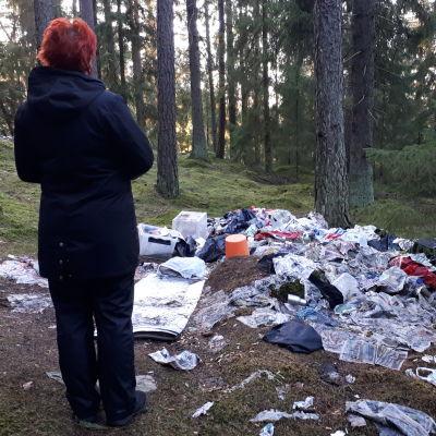 En person står och granskar en hög med papper och skräp som ligger på marken i en skog.