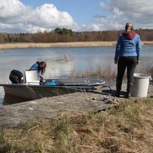 Två kvinnor förbereder sig för att åka ut med en öppen båt som ligger vid en brygga, i bakgrunden vass