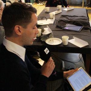 En man läser text på en pekplatta
