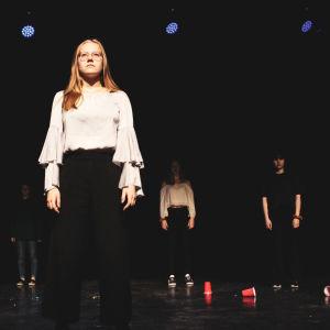 flicka står på scen och ser ut i publiken