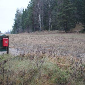 Två ensamma postlådor på en sandväg