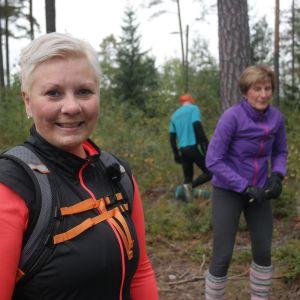 CrossNatureinstruktör Petra Mannström i skogen, två deltagare i bakgrunden