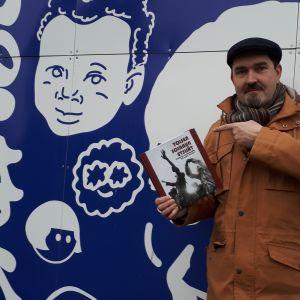Pertti Grönholm poserar med den nya boken om Åbos musikliv.