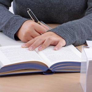 En uppslagen bok och någon som skriver.