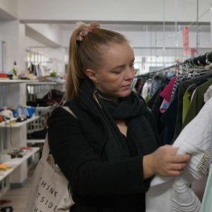 Julia Degerth synar ett plagg i närbild på loppmarknad