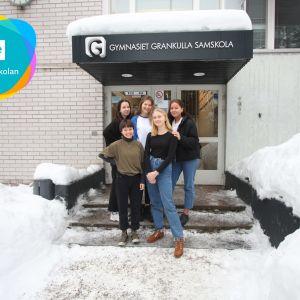 En bild med några elever utanför sen byggnad.