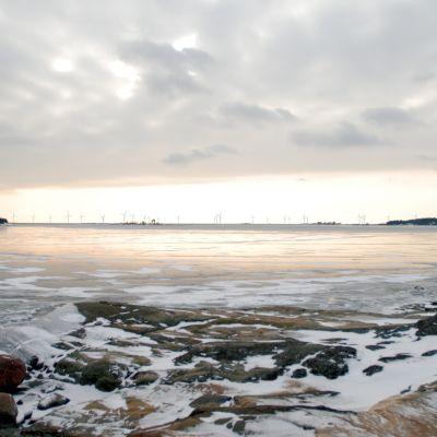 Vindmöllor skymtar långt ute i havet på ett bildmontage.