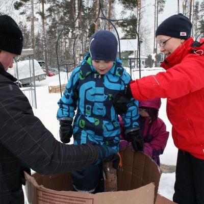 Nainen, mies, tyttö ja poika tekevät lumiveistosta.