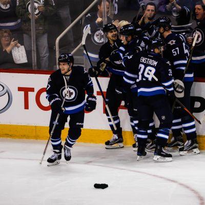 Patrik Laine ja muut Winnipeg-pelaajat juhlivat suomalaisen NHL-uran toista hattutemppua.