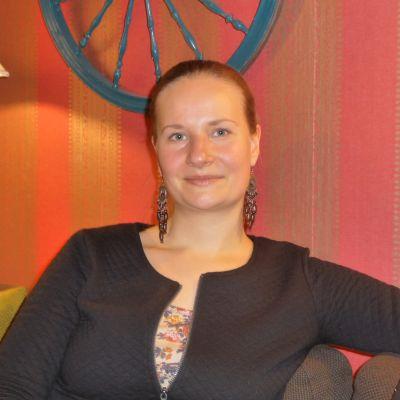 Jenny Sinisalo sitter i en soffa, röd bakgrund. Tittar rakt in i kameran. Ler lite.