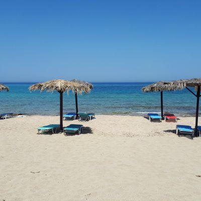 Kreetalainen uimaranta, jossa aurinkotuoleja ja -varjoja