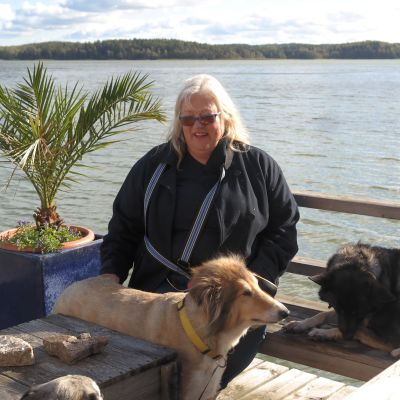 Britt-Marie Juup med två hundar på en brygga med havet i bakgrunden