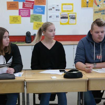 Tre elever sitter i sina pulpeter i en rad i ett klassrum, de är Cindy Henriksson, Sanni Ekblad och William Henriksson