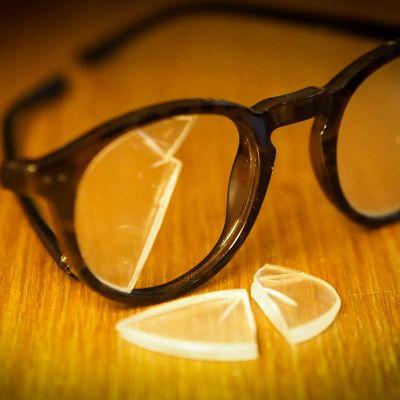 kuvassa silmälasit pöydällä, toinen linssi rikki