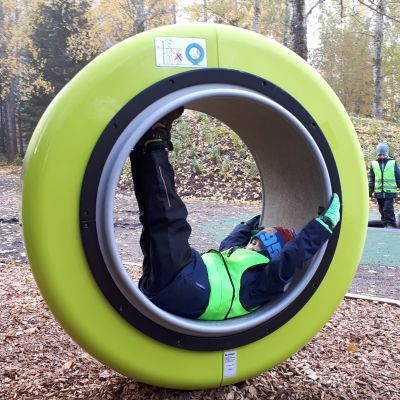 Lapsi leikkipuiston pyöreässä leikkikalussa Kuovin perhepuistossa Kouvolassa.