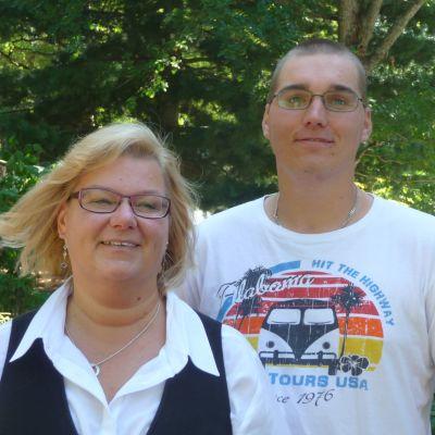 Till vänster kvinna i blont hår, till höger ung man i vit t-shirt, båda bär glasögon.