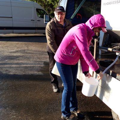 Kaksi ihmistä ottamassa vettä vedenjakelupisteestä Karsikossa Joensuussa.