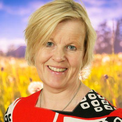 Ann-Cathrine Jungar ler rakt in i kameran med en sommaräng som syns i bakgrunden.