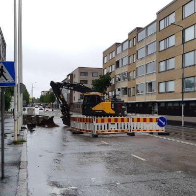 Kaivinkone keskellä katua Kajaanin kaupungintalon edustalla.