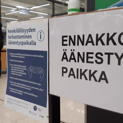 Ennakkoäänestys Seinäjoen Prismassa, äänestäjä vie lappuaan vaalivirkailijalle.