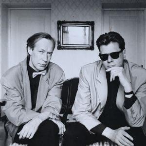 Mustavalkoisessa kuvassa kaksi miestä pikkutakeissa katsoo vakavina kameraan