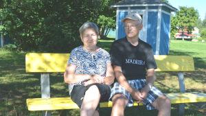 Äldre kvinna och äldre man sitter på gul bänk i skuggan av ett träd