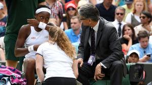 Cori Gauff får vård vid sidan av en tennisplan på grund av magproblem.