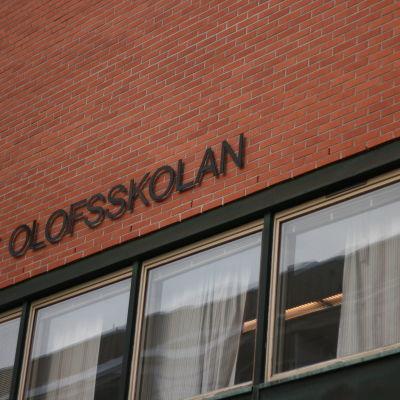 S:t Olofsskolans lärarrum med texten St Olofsskolan skrivet på väggen ovanför.