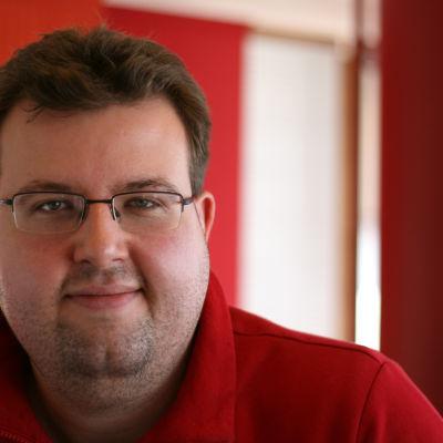 redaktören Jesper Alm på bild i en röd munkjacka.