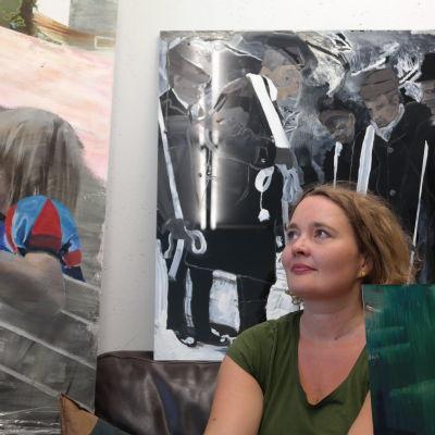 Konstnären Erika Adamsson bland sina målningar