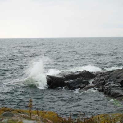 En stor våg slår mot klipporna.