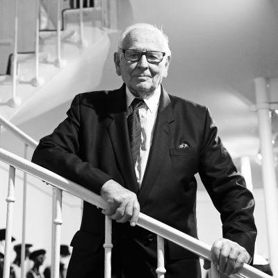Modeskaparen Pierre Cardin poserar vid en vit trappa i svart kostym. Bilden är svartvit.