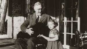 Franlin D. Roosevelt som sitter i en rullstol. I famnen har han en hund och bredvid honom står ett barn, en flicka.