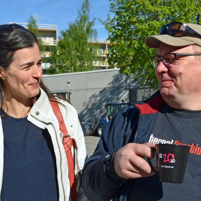 Johanna af Schultén och Paul Holländer poserar på Yles parkeringsplats.