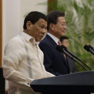 Rodrigo Duterte håller tal i Sydkorea. Bredvid honom Sydkoreas president  Moon Jae-in