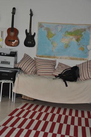 en säng, gitarre och en karta på väggen
