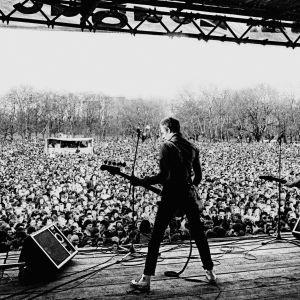 Paul Simonon The Clash -yhtyeestä lavallav selin, edessä yleisömeri. Kuva vuodelta 1978, dokumenttielokuvasta White Riot.