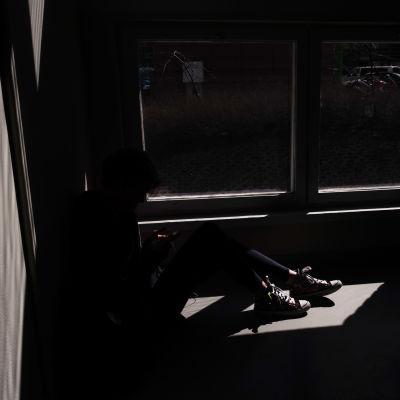Nuori istuu varjossa.