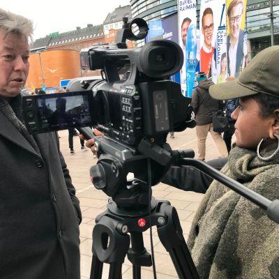 Nainen haastattelee miestä.