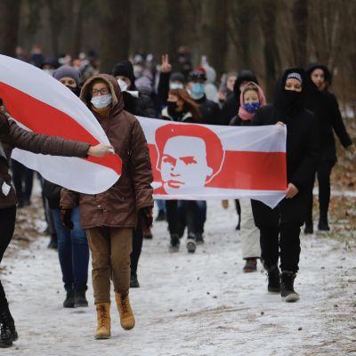 Demonstranter i Minsk bär svart-röda flaggor.