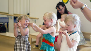 Kolme tyttöä leikkii ja laulaa.